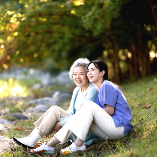 A teenage girl sits with her grandmother on a grassy hill outside.