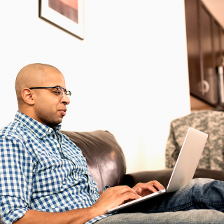 A man sitting on his couch at home uses his laptop computer to search for savings on his prescriptions.