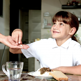 A young girl in a school uniform, sitting at the kitchen table, takes a prescription pill from her mother's hand.