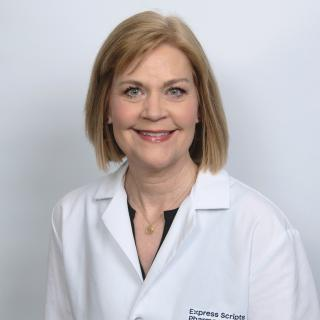 Susan Peppers smiles in her pharmacist lab coat.