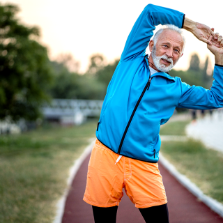 Older man stretching outdoors.