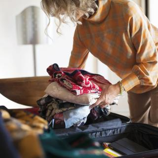 A woman packs her suitcase for travel.